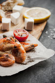 Grilled prawns on the peace of paper with tomatoes and cheese on the wooden board — Stock Photo