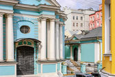 Blue church with white pillars in the middle of colorful houses — Stock Photo