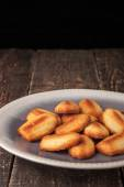 Madeleine cookies on the ceramic plate on the wooden table — Stock Photo