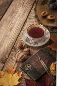 Plums, nuts and leaves with vintage notebook and tea with film filter effect vertical — Stock Photo