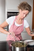 Woman in kitchen cooking — Stock Photo