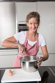 Woman in kitchen tasting — Stock Photo