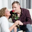 Man and woman talking on couch - he is smelling a rose — Stock Photo #73131141