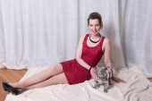 Woman in red dress with dog on blanket — Stock Photo