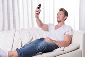 Portrait young man sitting on couch and eating chips and zapping — Stock Photo