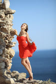 Girl in red dress posing on the coast — Stock Photo