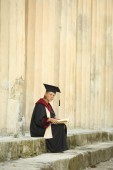 Woman graduate with a book — Stock Photo