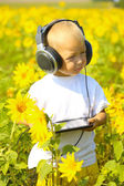 Funny baby in headphones with a tablet — Stock Photo