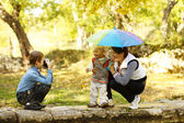Mother with children resting in the autumn park — Stock Photo