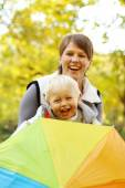 Mother with boy in the park under an umbrella — Stock fotografie