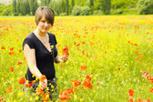 Beautiful young woman with a bouquet of poppies — ストック写真