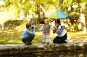 Mother with children photographed by the pond — Stock Photo