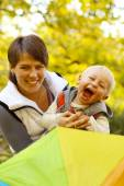Woman with a little boy  in the autumn park — Stock Photo