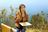 Girl artist draws on a mountain coast — Стоковое фото