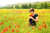 Beautiful young woman with a bouquet of poppies — Stock Photo