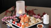 Beautifully decorated table with sushi and sake — Stock Photo