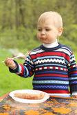 Funny boy eats sausages on picnic — Fotografia Stock