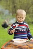 Funny boy eats sausages on picnic — Foto Stock