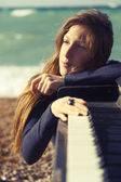 Beautiful girl with notes from an old piano on the beach — Stock Photo
