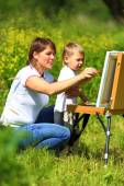 Mom and baby paint on an easel in the field — Stock Photo