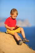 Little boy with a Tablet PC on the coast — Foto de Stock
