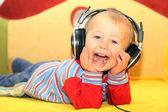 Funny kid listening to music in headphones — Stock Photo