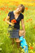 Beautiful woman with a child in the spring  field — Stock Photo
