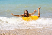 Laughing girl in bikini on inflatable ring — Stock Photo