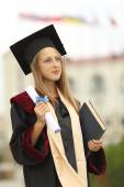 Girl graduate with diploma in hand — Stock Photo