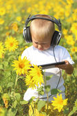 Funny baby in headphones and tablet — Stock Photo