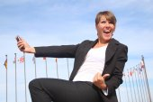 Enthusiastic woman businessman with a smartphone — Stock Photo