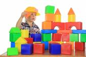 Little boy builds a house of childrens blocks — Stock Photo