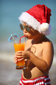 Funny santa with a cocktail on the beach — Stock Photo