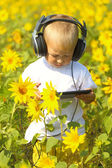 Baby in headphones and tablet — Stock Photo