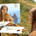 Girl artist draws on a mountain coast — Stock Photo #60537861