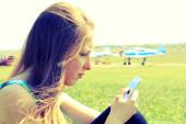 Beautiful girl with a smartphone on the airfield — Stock Photo