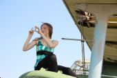 Beautiful girl with a smartphone on the wing of an old airplane — Stock Photo