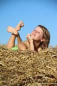 Peasant girl resting in haystack — Stock Photo