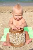 Funny kid Drumming on the beach — Stock Photo
