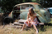 Pensive country girl from an old broken car — Stock Photo