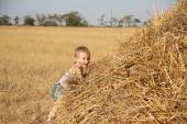 Carefree boy resting in haystack — Stock Photo