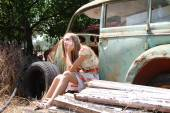 Pensive country girl from an old broken car — Foto Stock