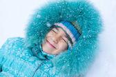 Happy kid girl child outdoors in winter lying on snow under snow — ストック写真
