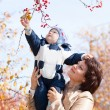 Young mother woman girl holding baby kid son on autumn berries b — Stock Photo #58638555
