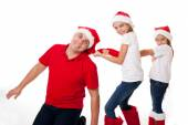 Happy  father and two daughters in santa's hats laughing — Stock Photo