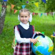 Happy schoolgirl child kid girl holding globe and smiling, point — Stock Photo #59358603