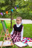 Happy schoolgirl child kid girl sitting on grass and writing on  — Stockfoto
