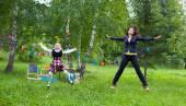 Happy teacher mother woman with schoolgirl kid jump outdoors — Stock Photo