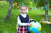 Happy schoolgirl child kid girl holding globe and smiling, point — Stockfoto