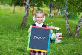 Happy schoolgirl child kid girl holding a chalkboard with a form — Fotografia Stock